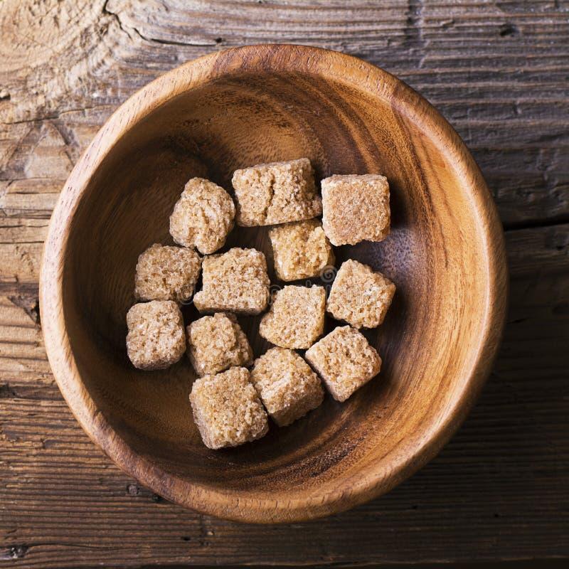 Тростниковый сахар кубов естественный коричневый в деревянном шаре на предпосылке Концепция натуральных продуктов Селективный фок стоковые изображения