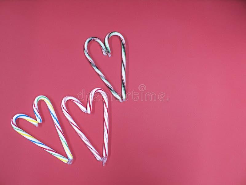 Тросточка карамельки 3 сложила в форме сердца на розовой предпосылке стоковые изображения