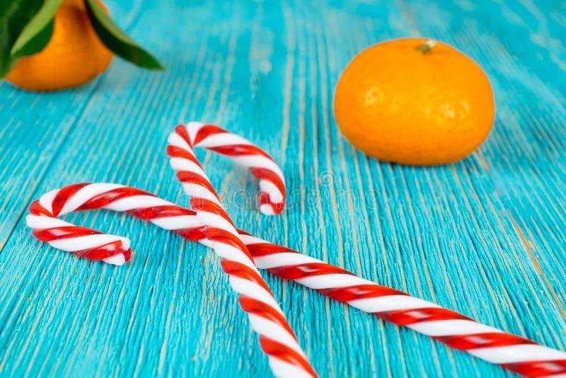 Тросточки конфеты сердце и tangerines на деревянных планках, предпосылке xmas стоковые изображения rf