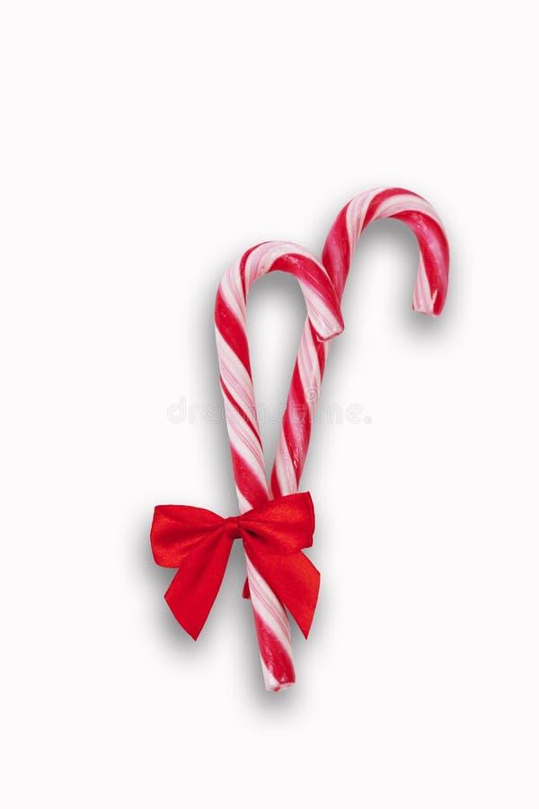 2 тросточки конфеты с смычком на белой предпосылке стоковое фото rf