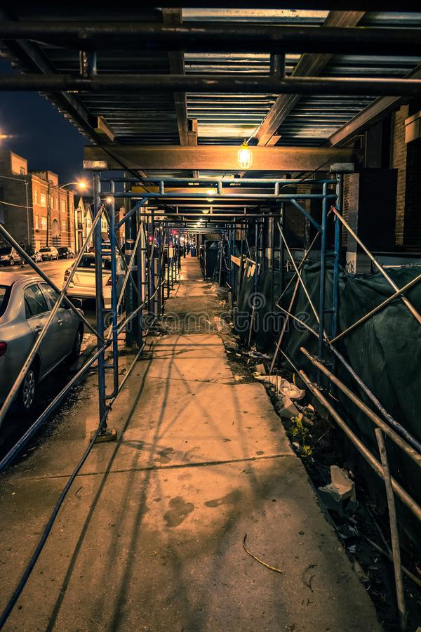 Тротуар города с лесами конструкции на ноче стоковое изображение