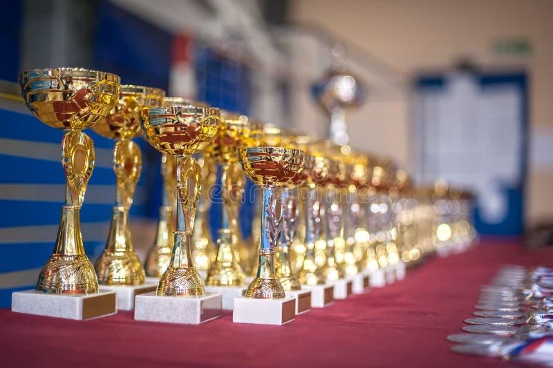 Трофеи и медали чемпиона золота выровнялись вверх в строках стоковое фото