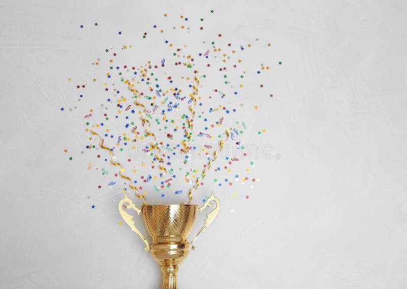 Трофей и confetti на светлой предпосылке, взгляде сверху с космосом для текста стоковое фото