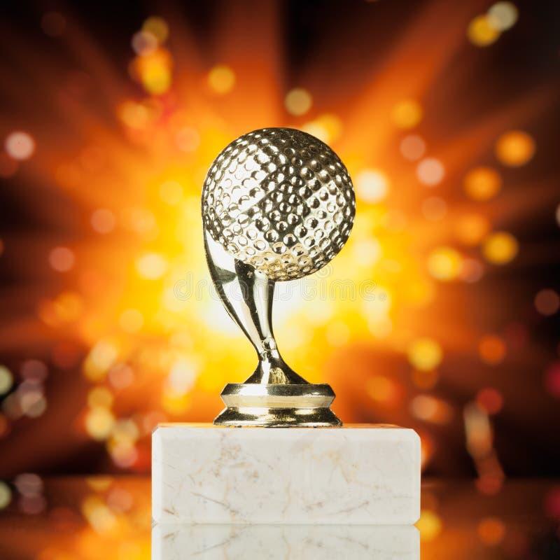 Трофей шара для игры в гольф против сияющей предпосылки стоковая фотография