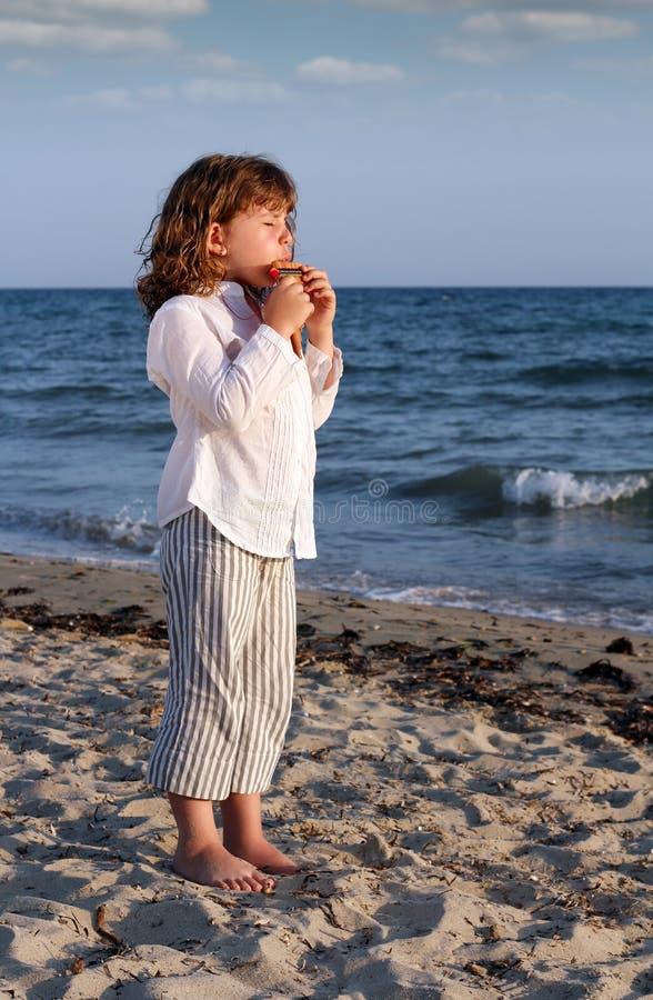 Труба лотка игры маленькой девочки на пляже стоковая фотография