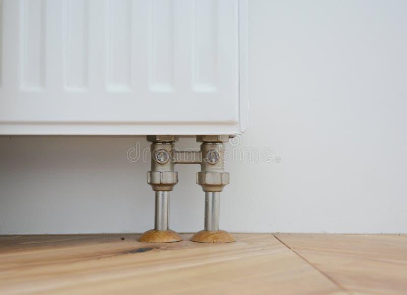 Труба радиатора покрывает рукави Установите радиатор для системы отопления с пряча трубами в деревянный пол стоковое фото