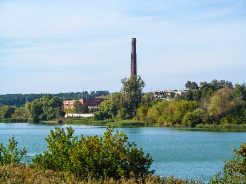 Труба разрушенного сахарного завода Ugroidy на банке области Сумы пруда, Украине Красивый деревенский промышленный ландшафт стоковая фотография