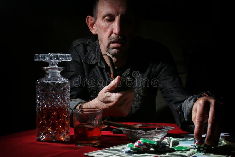 Труба дыма человека и покер игры стоковое изображение