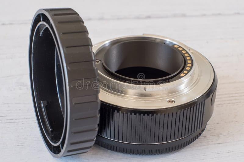 Трубка расширения объектива фотоаппарата и крышка конца на белой покрашенной доске стоковое изображение