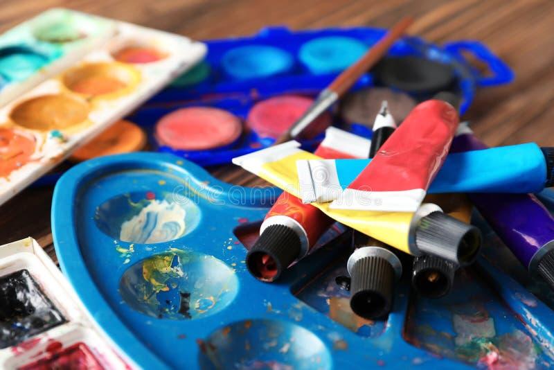 Трубки краски с палитрами акварелей на таблице стоковые фото
