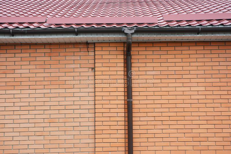 Трубопровод из крыш на кирпичном домике стоковая фотография