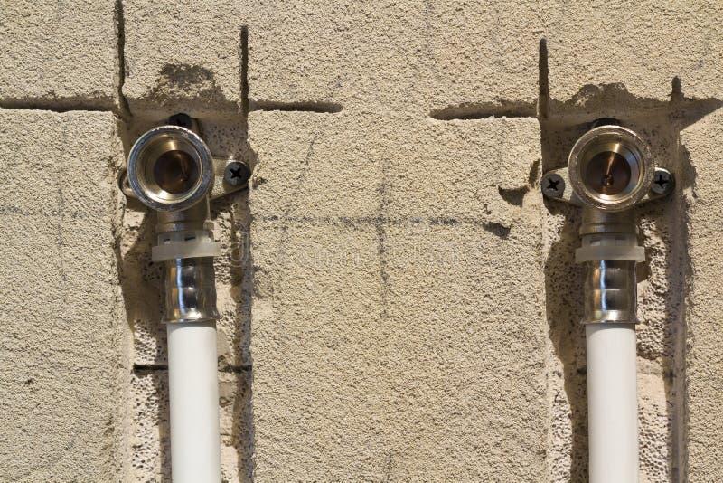 Трубы водопровода сделанные из полипропилена в стене, паяющ в доме Установка канализационных трубов в ванной комнате квартиры вну стоковое изображение