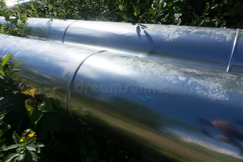 Трубы водопровода с ложью изоляции на траве стоковые фотографии rf