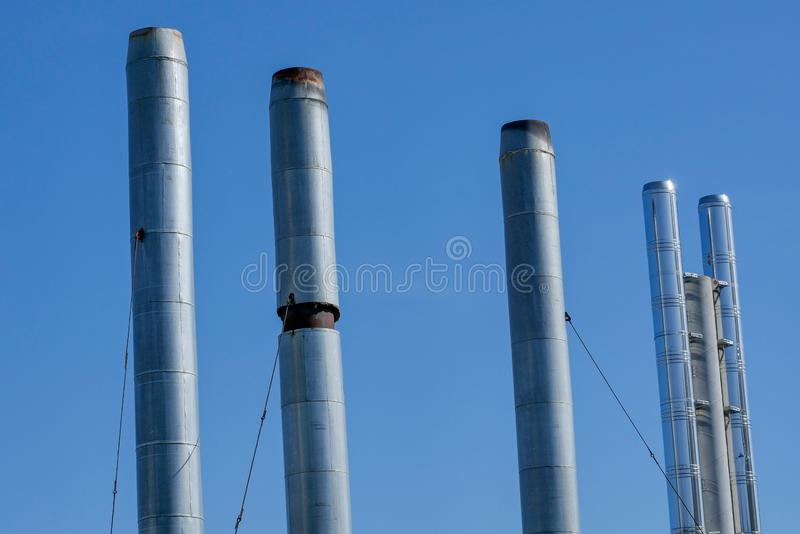 Трубы котельных газа на предпосылке голубого неба лета Дым от труб не идет стоковые фото