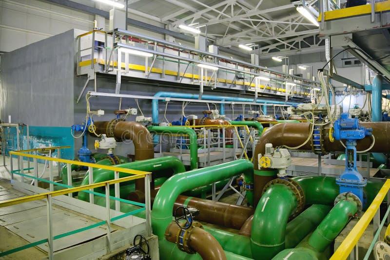 Трубы, фильтры и насосы нечистот внутри современного промышленного завода обработки сточных вод стоковое изображение