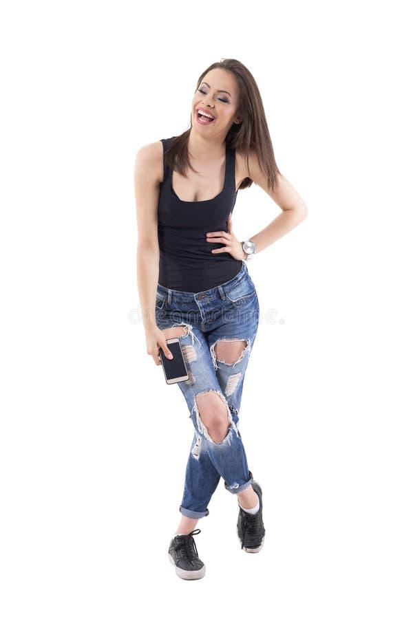 Трудная смеясь женщина с мобильным телефоном гнуть от heartily хохота стоковое фото rf