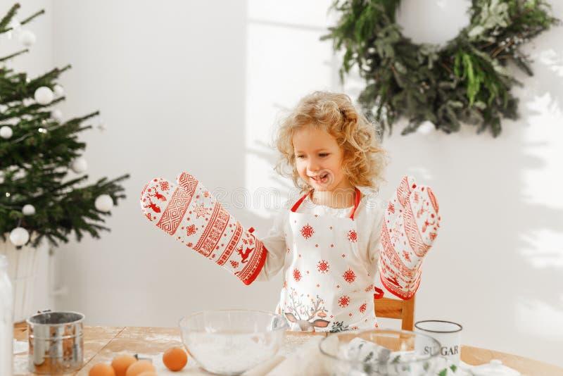 Трудный работая кашевар маленького ребенка носит большие перчатки кухни, подготавливает очень вкусное печенье вместо матери, увер стоковые изображения