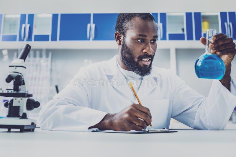 Трудолюбивый молодой химик делая некоторые примечания стоковое изображение