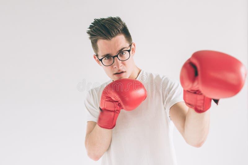 Трусливый смешной молодой человек в красных перчатках бокса Болван носит стекла стоковое изображение