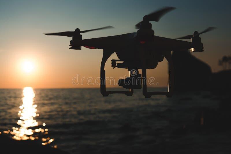Трутень в небе захода солнца горы океанской волны закрывают вверх quadrocopter outdoors концепция для videography свадьбы режиссе стоковое фото rf