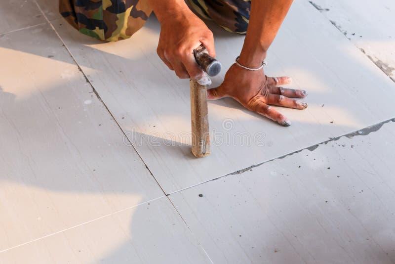 Трудовой устанавливая плиточный пол для нового жилищного строительства стоковая фотография rf