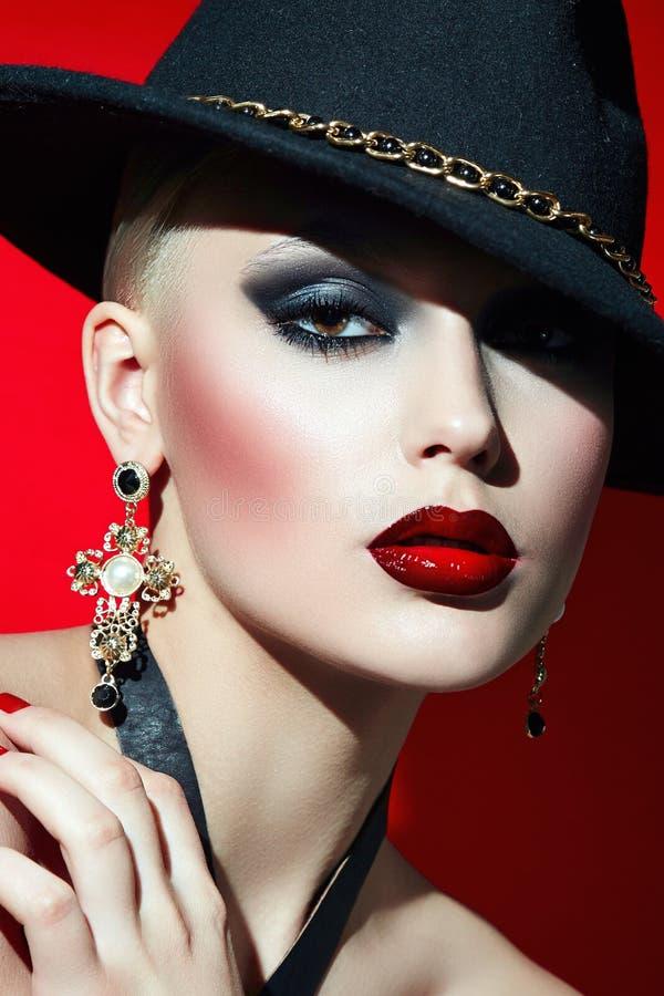 Тряхните девушку в черной шляпе с красными губами стоковое фото