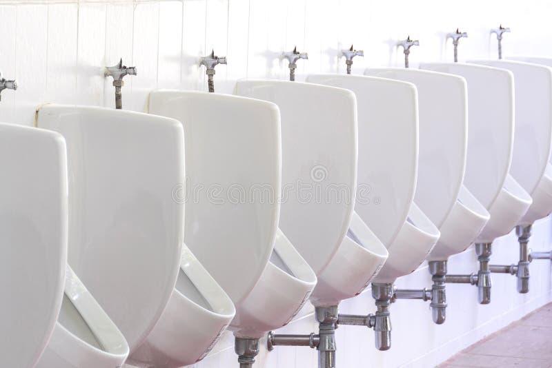 Туалет белых людей писсуаров керамических общественный в ванной комнате стоковое фото