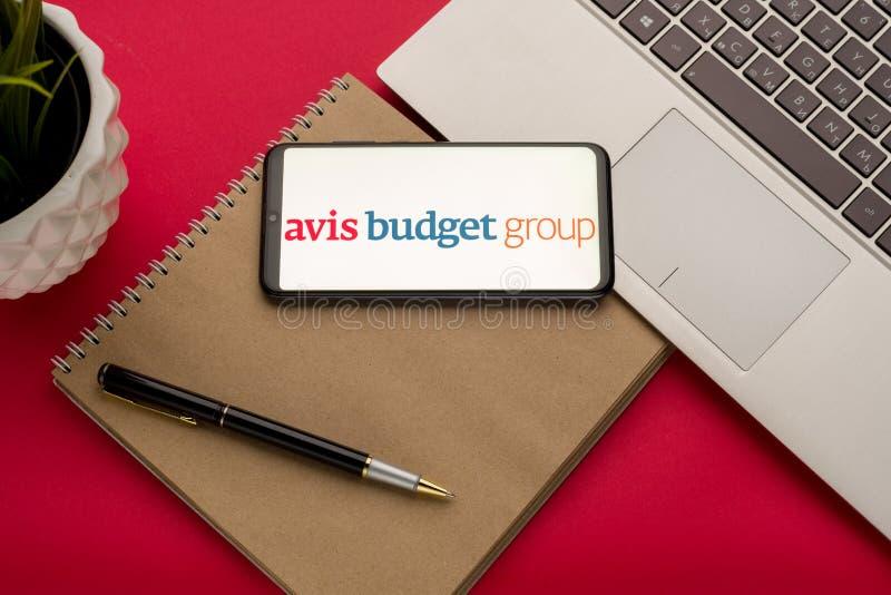 Тула, Россия - 19 октября 2019 года: Avis Budget Group отображается на смартфоне рядом с современным ноутбуком на красном фоне стоковое изображение
