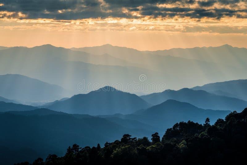 Туманная горная цепь с драматическим небом захода солнца стоковая фотография rf