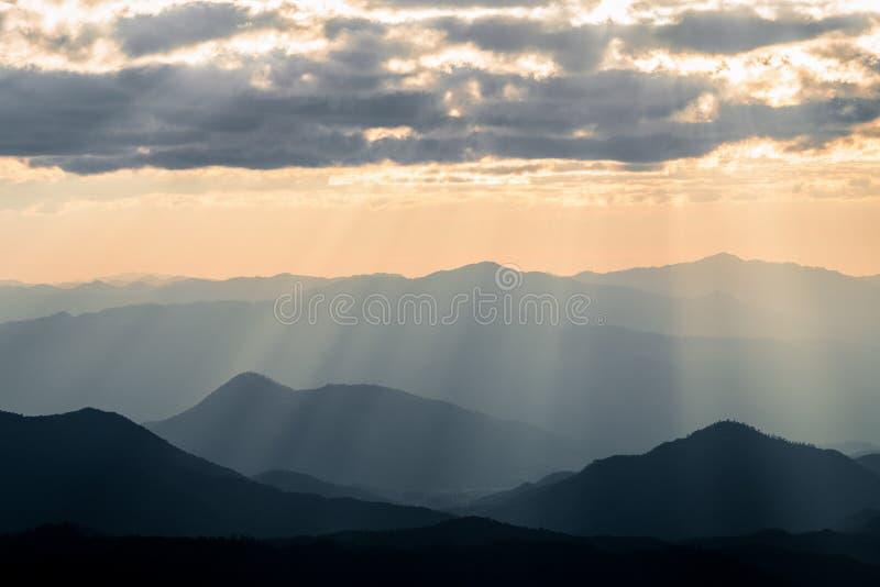 Туманная горная цепь с драматическим небом захода солнца стоковое изображение rf