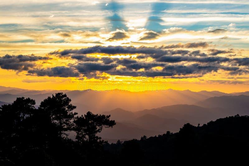 Туманная горная цепь с драматическим небом захода солнца стоковые фото