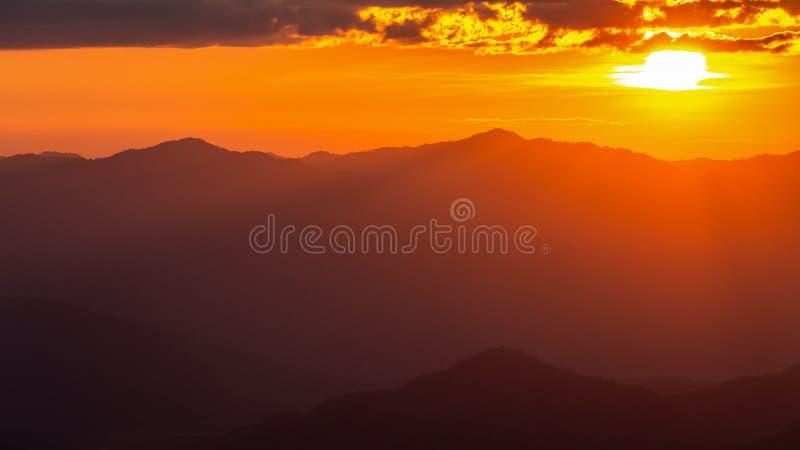 Туманная горная цепь с драматическим небом захода солнца стоковое изображение