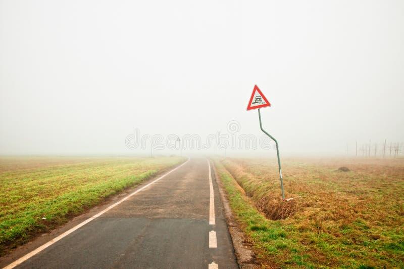 Fog вдоль пустой сельской дороги с знаком опасности стоковая фотография rf