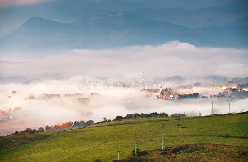 Туманное солнечное утро в горном селе холмы туманные стоковые фото