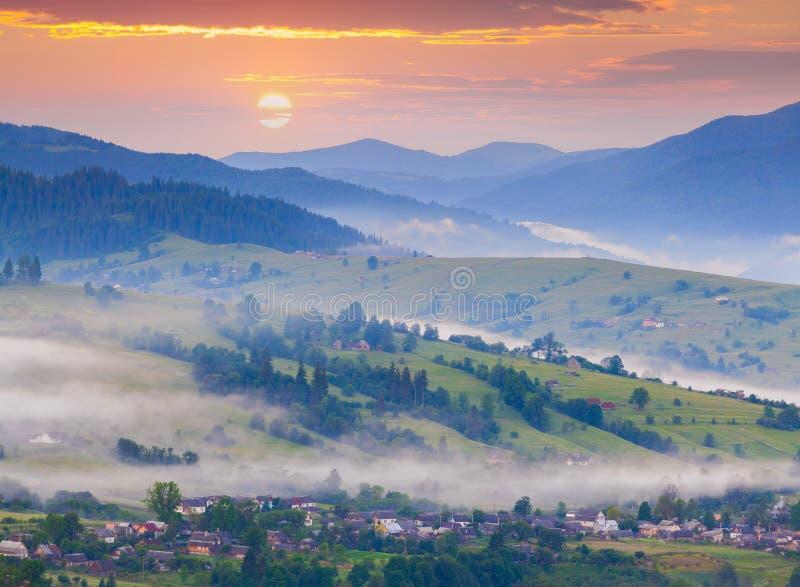 Туманное утро лета в горном селе стоковое фото rf