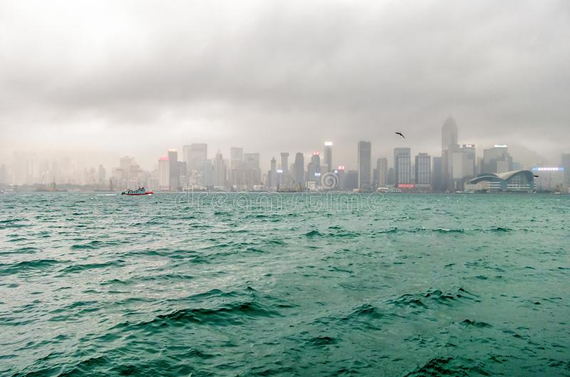 Туманный городской пейзаж Гонконга через бурную гавань Виктории общий пейзаж города стоковое изображение rf