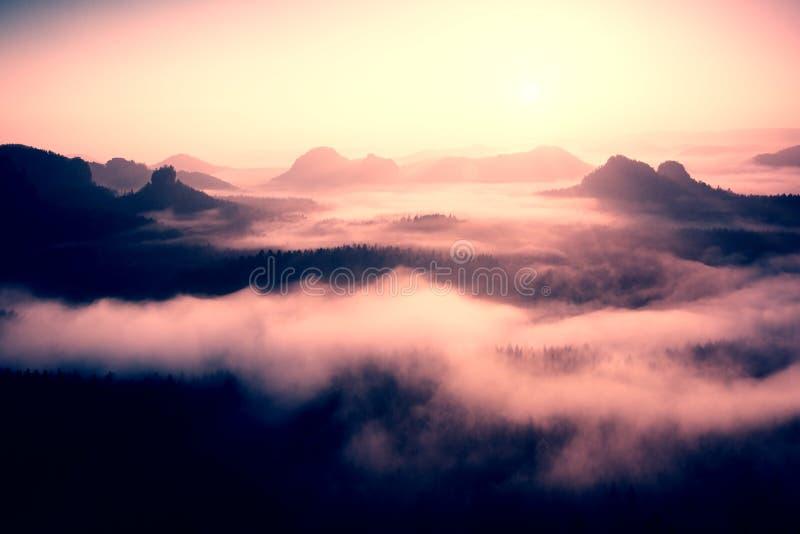 Туманный рассвет в красивые холмы Пики холмов вставляют вне от туманной предпосылки, туман желт и апельсины должный к su стоковые фотографии rf