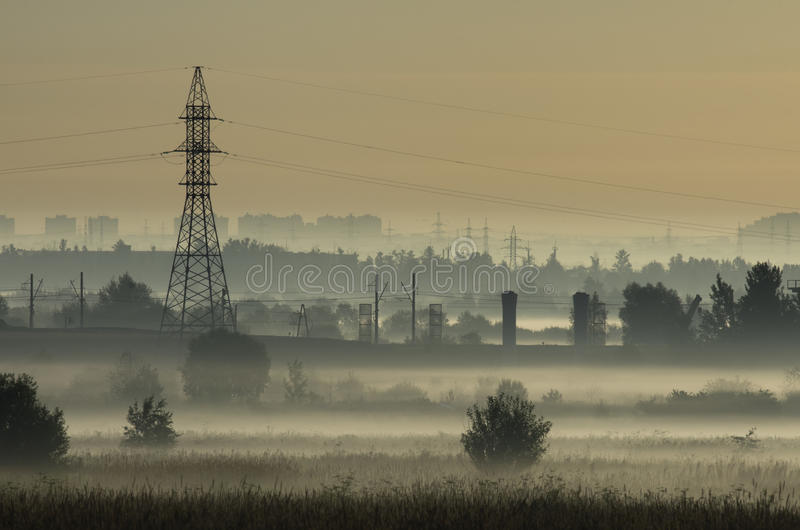 Туман над полями и башней линий электропередач стоковые фотографии rf