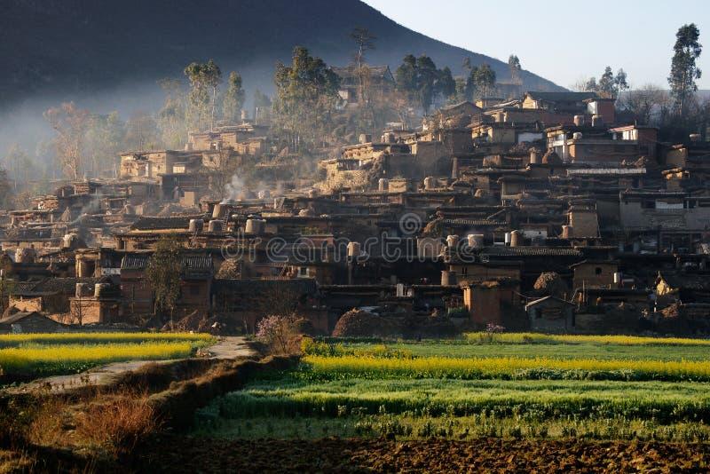 Туман приходя от гор в вечере покрывая малую деревню на ноге горы стоковые изображения