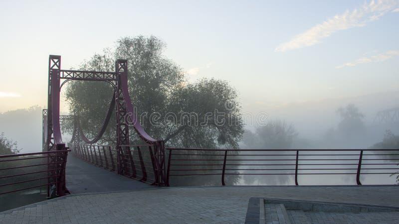 Туман утра на реке С небольшим мостом металла стоковые изображения rf