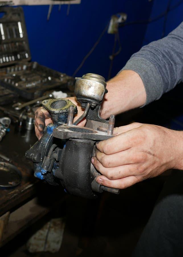 Турбина автомобиля в руках мастера стоковое фото