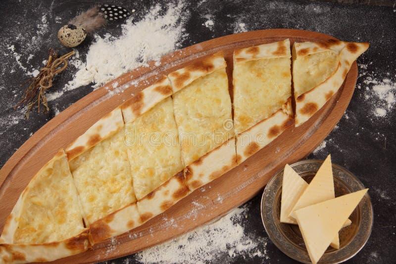 Турецкая пицца вызвана pide Блюдо с Pide с сыром на темной таблице, взбрызнутой с мукой стоковая фотография