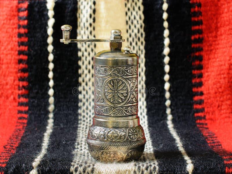 Турецкий винтажный точильщик специи руки на старой handcrafted сплетенной ткани стоковые фото