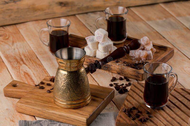 Турецкий кофе в традиционный выбитый турка металла съемка конца-вверх чашки кофе с зажаренными в духовке фасолями и cezve стоковое фото