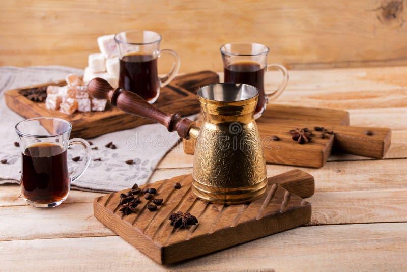Турецкий кофе с турком и стеклом кофе на предпосылке красивой деревянной плиты стоковые фотографии rf