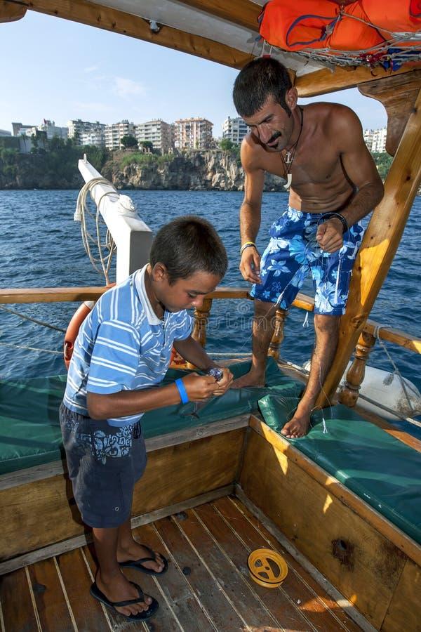 Турецкий мальчик извлекает крюк от рыбы изрекает после того как он был уловлен с шлюпки круиза в гавани Антальи стоковые изображения