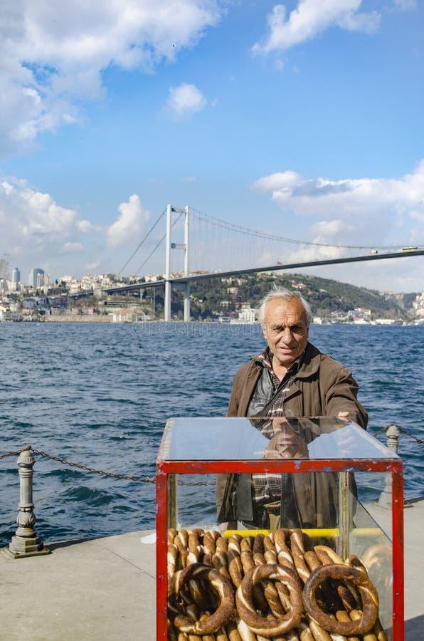 Турецкий поставщик продает бейгл, Стамбул на Bosphorus стоковая фотография rf