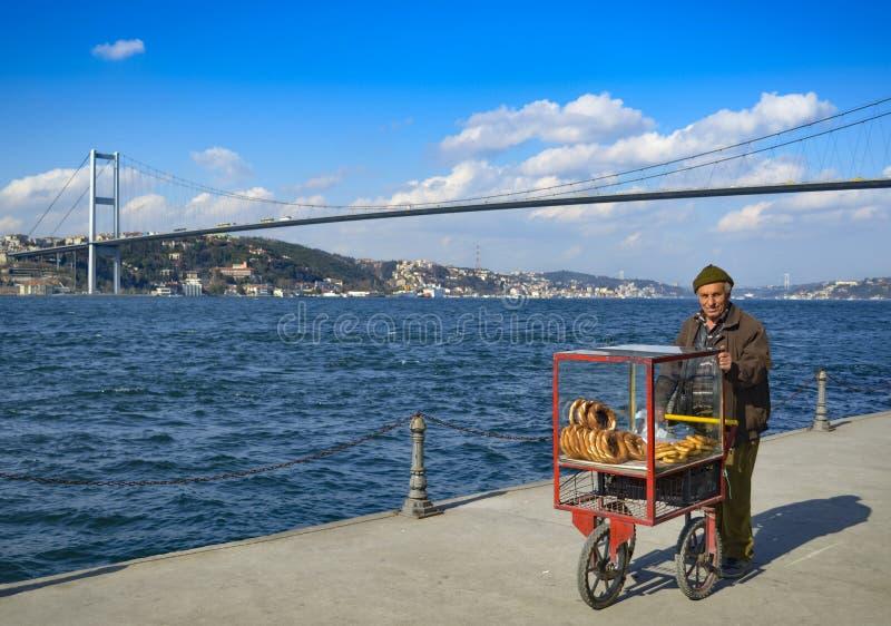 Турецкий поставщик продает бейгл, Стамбул на Bosphorus стоковое фото