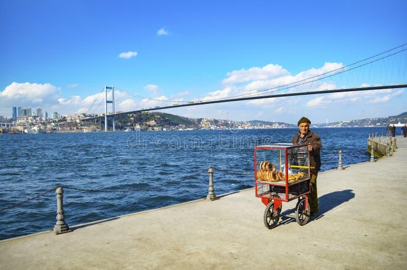 Турецкий поставщик продает бейгл, Стамбул на Bosphorus стоковые фото