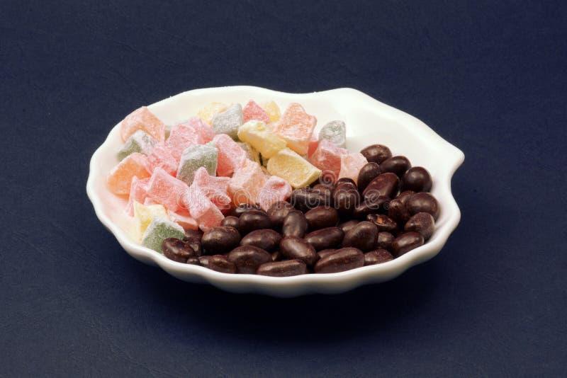 Турецкое наслаждение и арахисы в шоколаде на белом фарфоре покрывают темную предпосылку стоковое фото rf